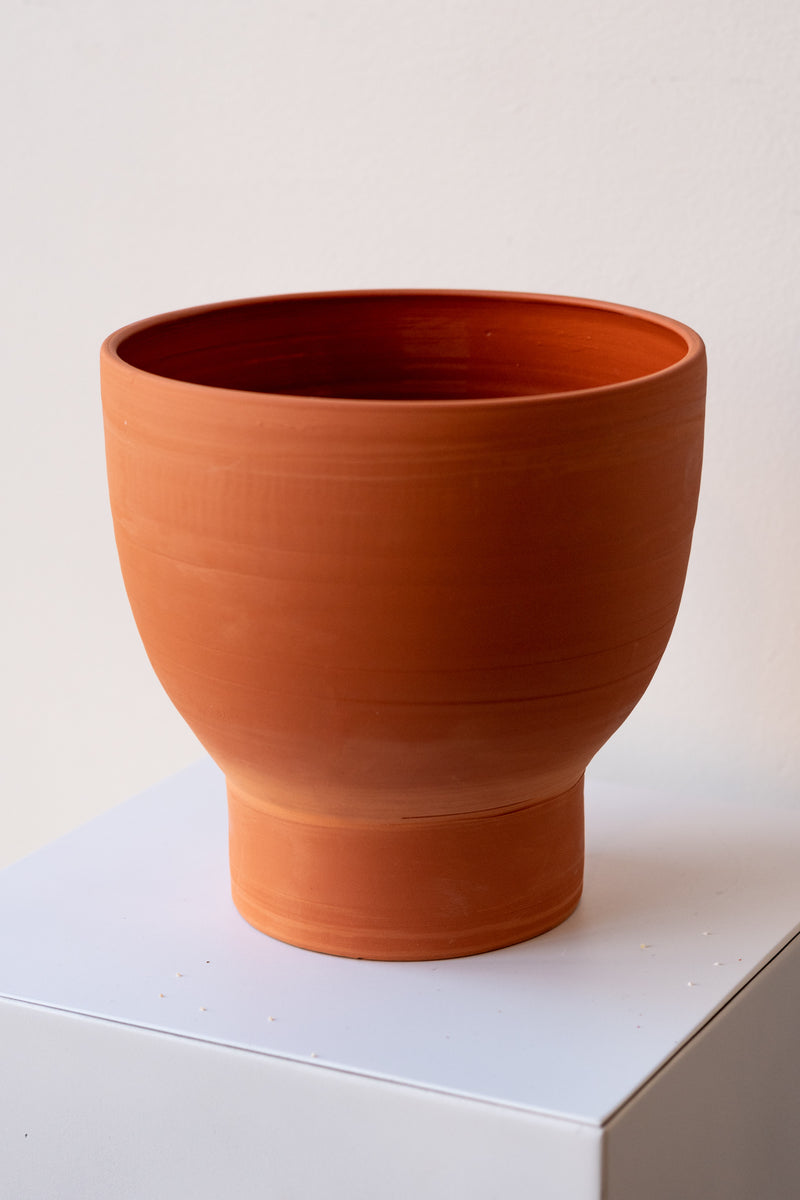 One terra cotta vase sits on a white surface in a white room. The vase is cylindrical at the bottom with a wider bowl shaped top. The vase is empty. It is photographed closer and at an angle.