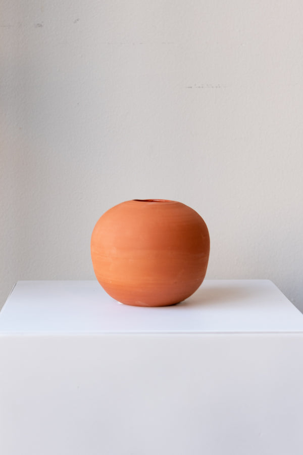 One small round terra cotta vase sits on a white surface in a white room. The vase is empty. It is photographed straight on.
