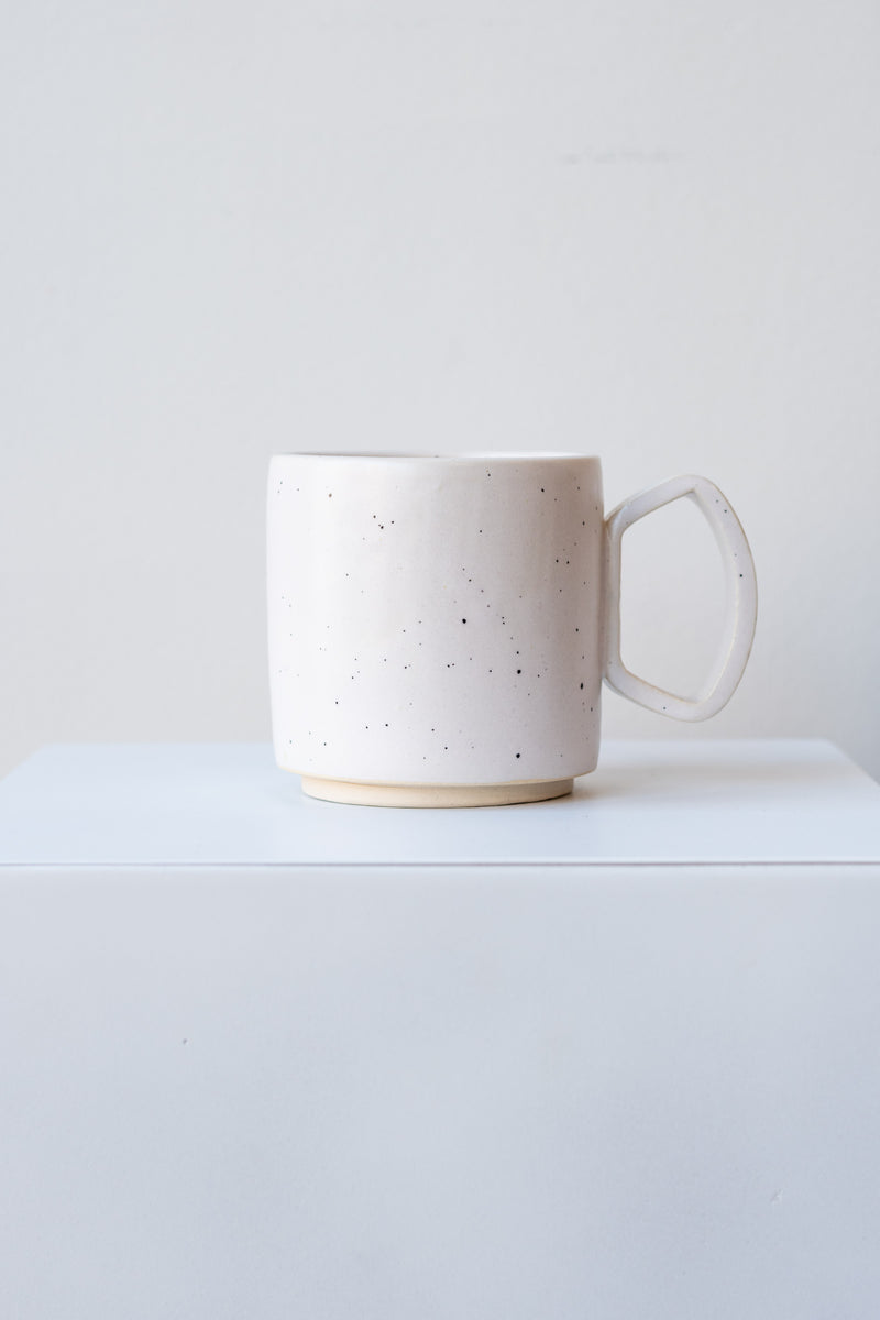 One ceramic mug sits on a white surface in a white room. The mug is white with black speckles. There is a narrow ring of unglazed clay at the bottom of the mug. It is photographed straight on.