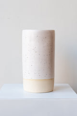 One cylindrical clay vase sits on a white surface in a white room. The vase is glazed with a white glaze with black speckles. The bottom quarter of the vase is unglazed, showing cream-colored clay. The vase is empty. It is photographed straight on.