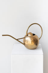 Round brass watering can with long thin spout and round handle sits on a white pedestal in a white room.