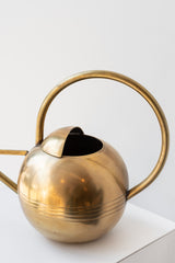 Close up of round handle on round brass watering can.