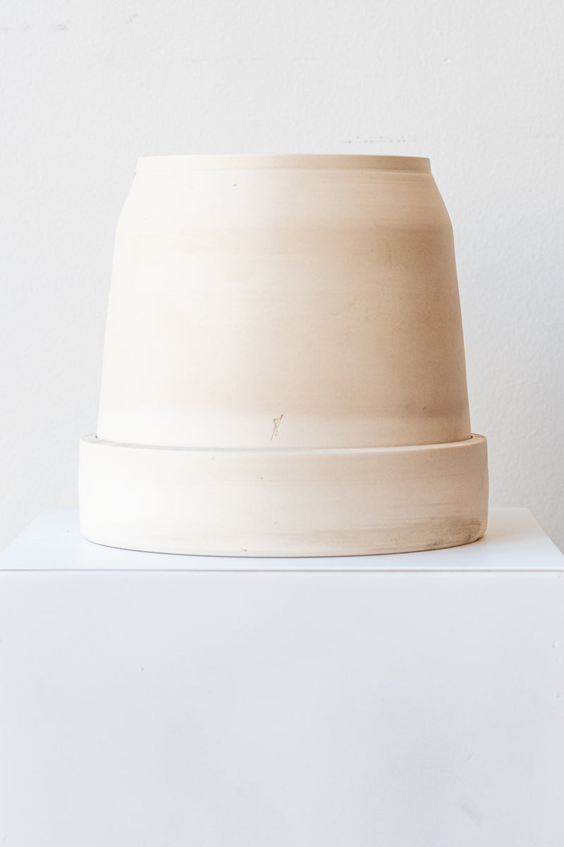 One cream colored stoneware planter sits on a white surface in a white room. The planter is round and squat, with a small logo imprinted in the clay on the bottom. The planter also sits on a round drainage tray. It is photographed straight on.