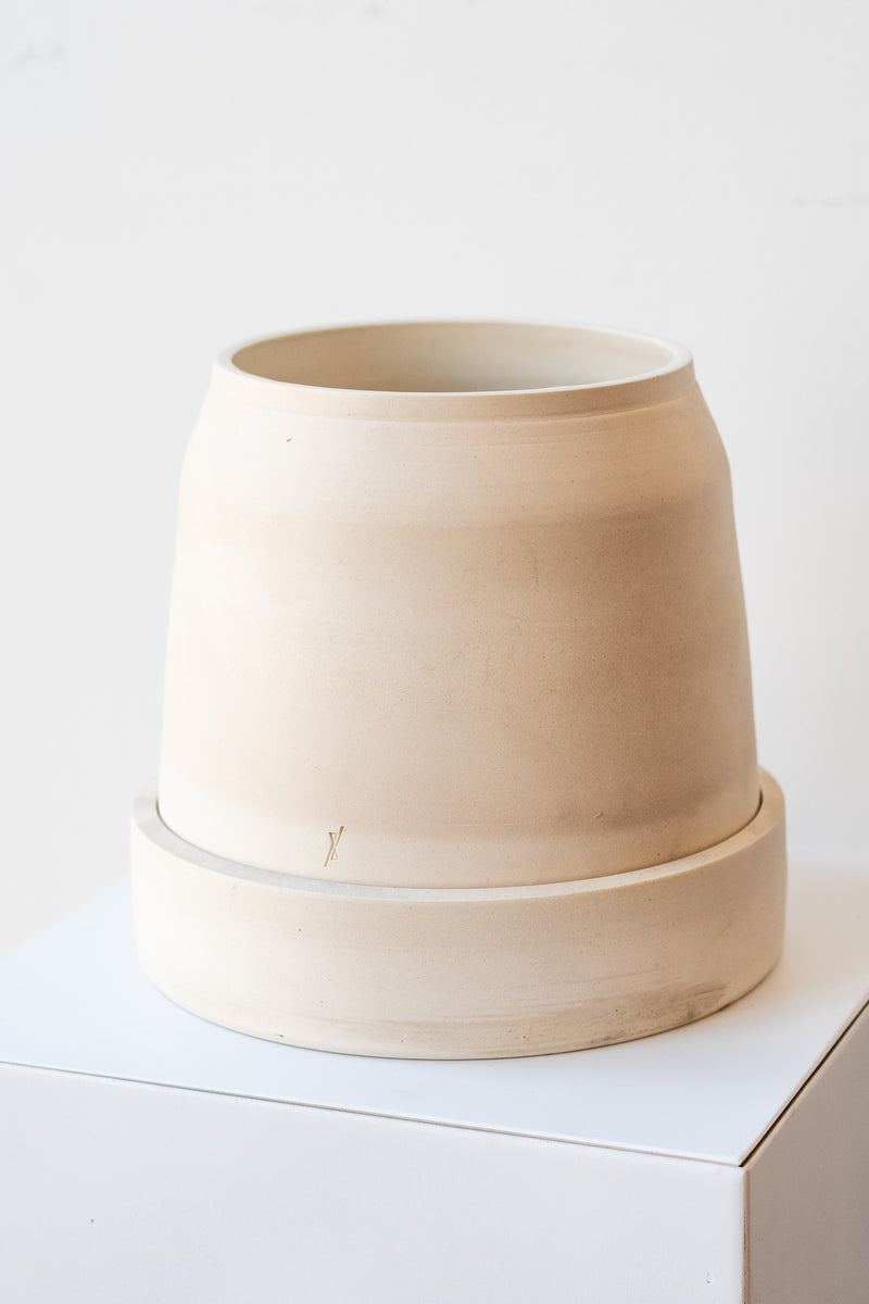One cream colored stoneware planter sits on a white surface in a white room. The planter is round and squat, with a small logo imprinted in the clay on the bottom. The planter also sits on a round drainage tray. It is photographed at a slight angle to show the clay detail.