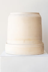 One cream colored stoneware planter sits on a white surface in a white room. The planter is round and tall, with a small logo imprinted in the clay on the bottom. The planter also sits on a round drainage tray. It is photographed straight on.