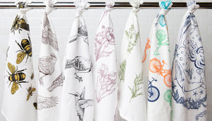 Cotton kitchen towels hanging on a bar. Featuring bees, birds, flowers, herbs, bikes and whales.