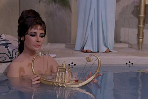 A scene from the film Cleopatra where the lead actress Elizabeth Taylor is in the bath