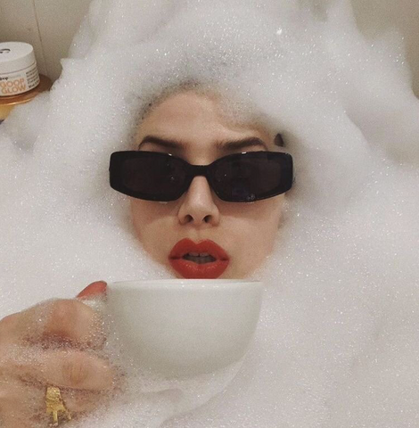 A woman with sunglasses on, sipping tea, in the bath surrounded by bubbles