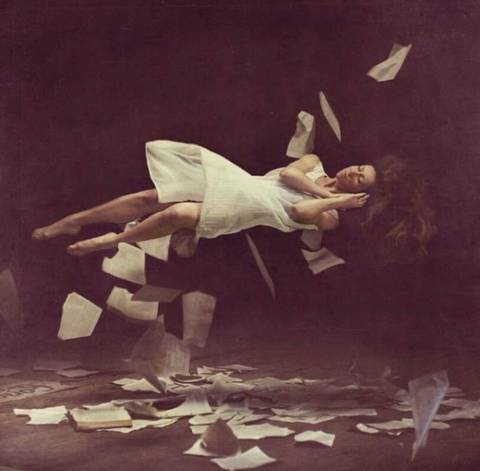 A sleeping woman levitating in the air, surrounded by paper