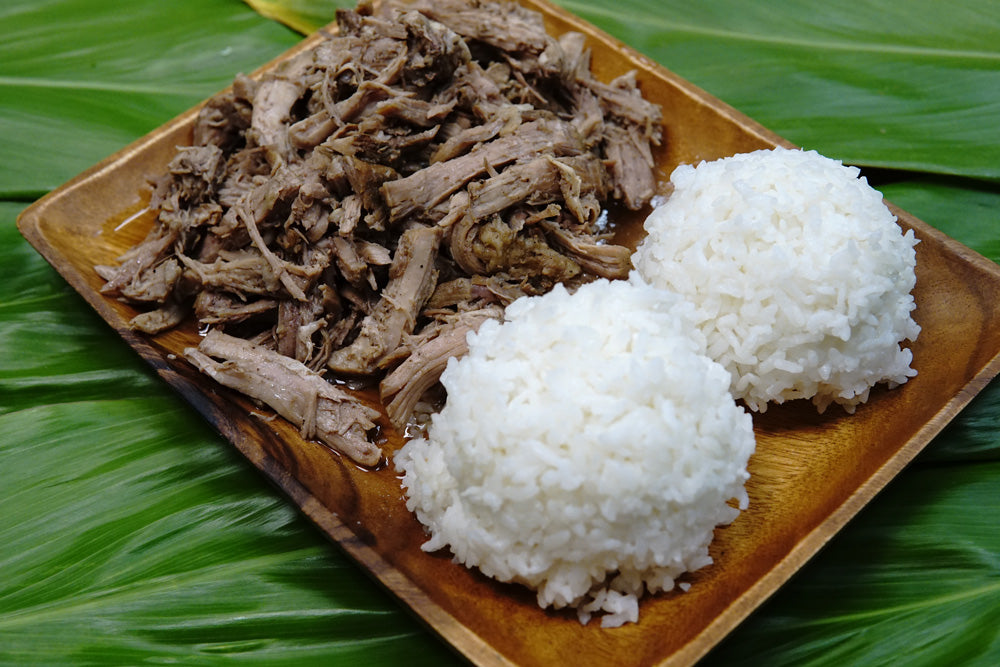 A dish of kalua pork and two scoops of white rice, arranged on a plate over ti leaves.