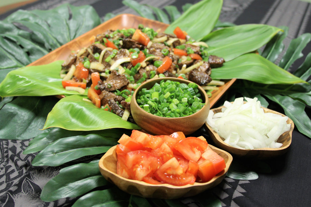 Grilled steak poke with green onion, chopped white onion, and chopped tomato in side dishes. The food is plated in wooden bowls and styled with ti leaves.