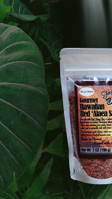 A 7 oz. bag of Gourmet Hawaiian Red 'Alaea Salt against a tropical background showing a forest, waterfall, and white orchid.
