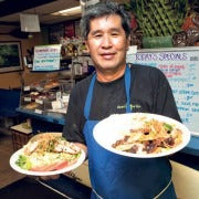 Chef Dean Mishima holding up two dishes while working in a restaurant.