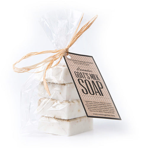 4 small square bars of lavender goat milk soap packaged in a clear bag tied with raffia
