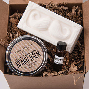 Square kraft brown box filled with brown paper shred and metal tin of beard balm, sample amber bottle of beard oil, bar of white goat milk soap with mustache design