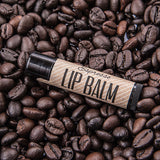 Black tube with brown label of Espresso Lip Balm on bed of coffee beand