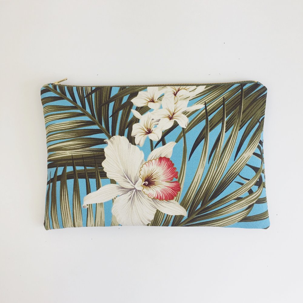 Clutch bag in blue tropical print with white and pink orchids and palm fronds. This bag has burgundy drill cotton lining and a khaki zip with metal teeth. There is an internal pocket.