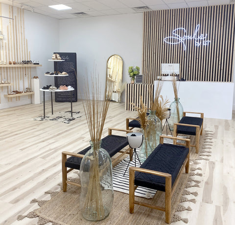 picture of inside of souls by lt panama city beach with white neon souls by LT sign, black benches, natural wood floors, and other beach decor.