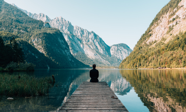 person on a lake looking at the mountains ahead