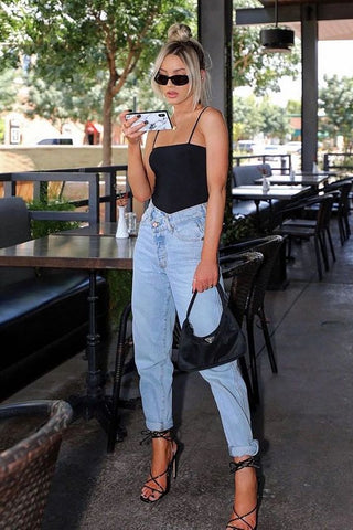 high-waist pants paired with a strapped black spaghetti top