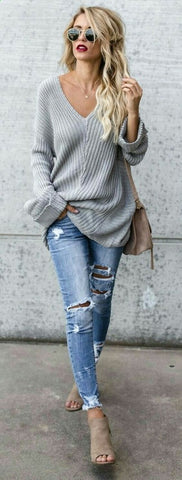tattered skinny jeans and an oversized sweatshirt