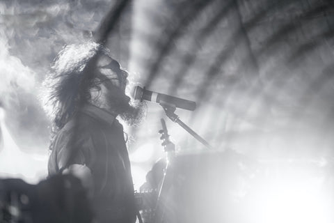 A black and white picture of a man singing into a microphone