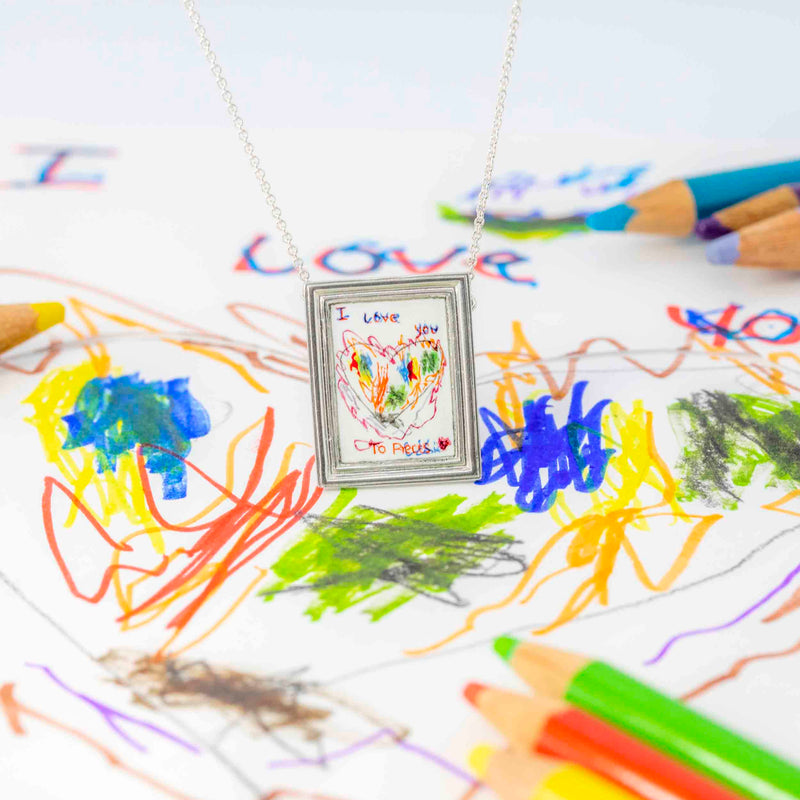 Ethically Handmade Personalised Silver Necklace On Top Of A Childs Drawing