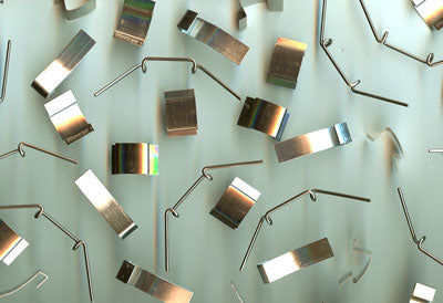 Metal S and W clips scattered on a flat surface