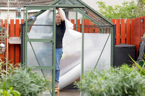 Kate inside greenhouse attaching bubble wrap