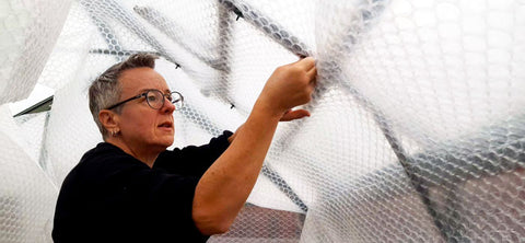 Kate affixing bubble wrap around roof and vents