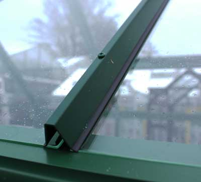 Close up on greenhouse bar capping. Dark green metal bar sits over glass framework.