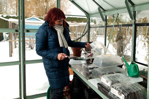 Red-haired woman inside a Rhino Greenhouse with snow outside. She is checking on her seedlings inside a propagator
