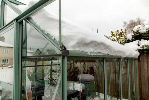 Rhino Greenhouse with thick layer of snow on the roof, falling in the gutter.
