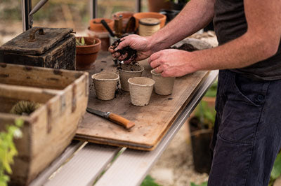 filling compostable pots with compost, soil cascading from a man's hands