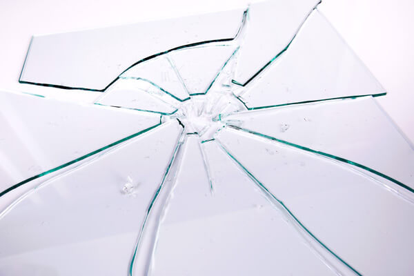 Pane of broken horticultural glass, showing deep cracks from point of impact and large sharp shards.