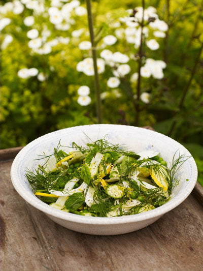 Raw Courgette Salad in a white bowl set on top of a rough wooden table top with foliage beyond