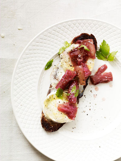 Toasted rustic bread smothered with creamy white goat's cheese with vibrant pink stewed rhubarb and fresh green herbs.