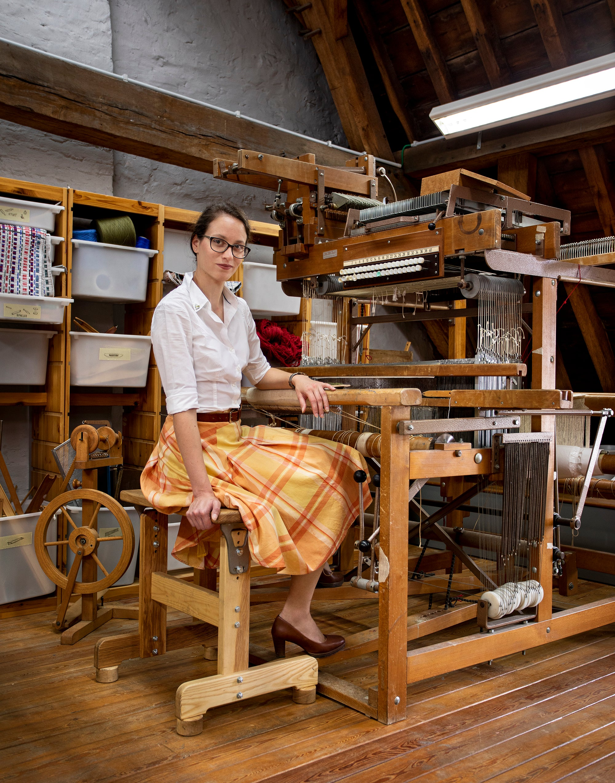 Szonja Daniel sitting next to a weaving loom in yellow plaid pattern skirt and white shirt.. Photo by Frederik Van Allemeersch made in commission of StadGent for the Van Eyck year.