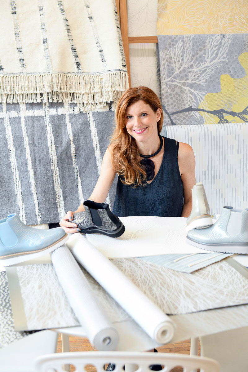 Jill Malek sitting at table with fabric swatches, wallpaper rolls and rain boots holiding Cougar Kensington Rainshine Chelsea in Night