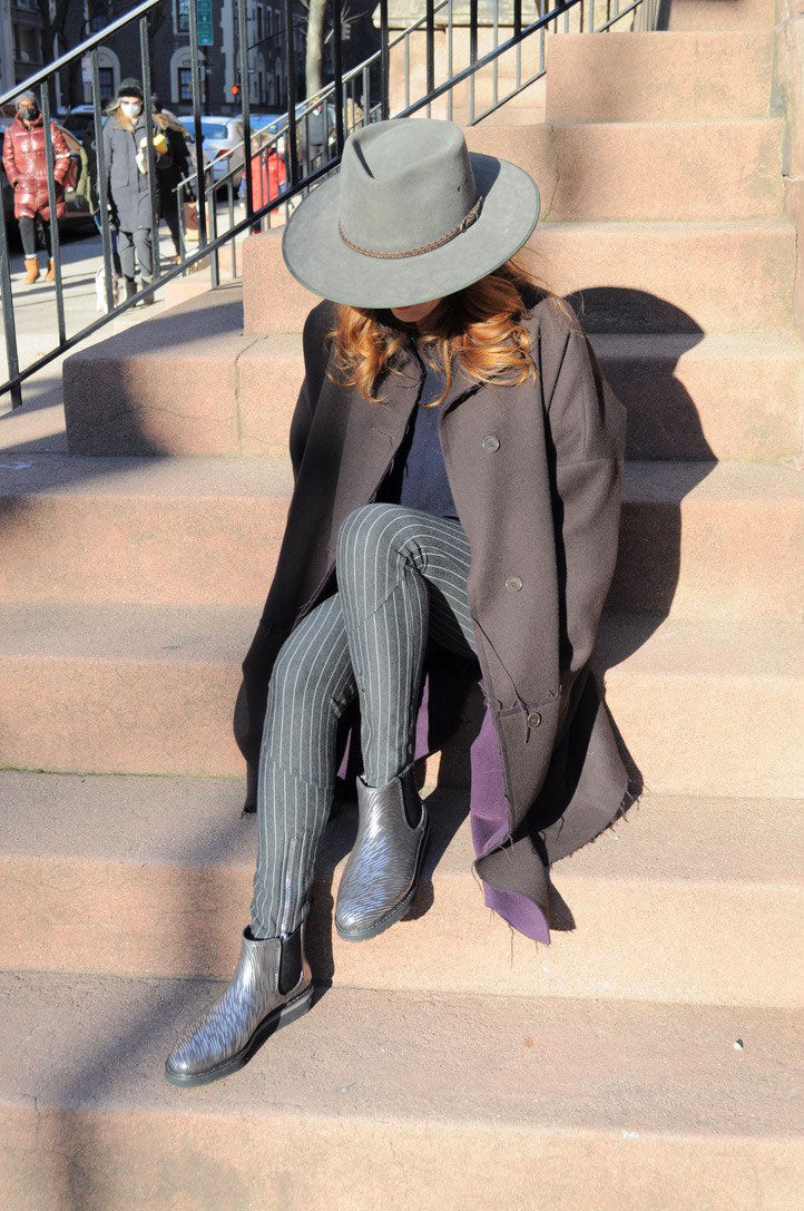 Jill Malek sitting on steps outside with grey hat, trench coat,  tapered pants wearing Cougar Kensington Rainshine Chelsea Boot in Night