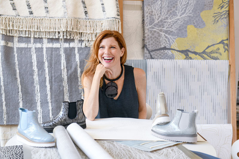 Jill Malek sitting at table with fabric swatches, wallpaper rolls and Cougar Kensington Rainshine Chelsea Boot on table