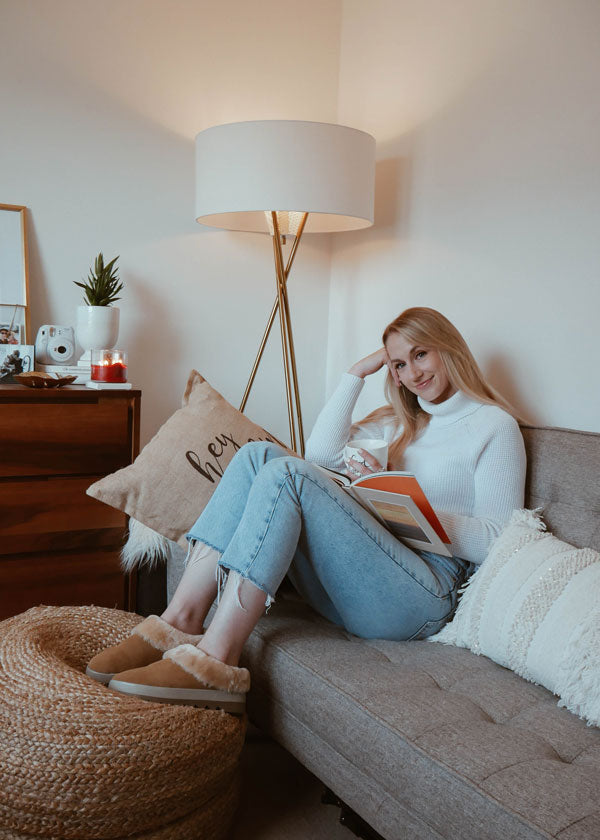 Amanda Weldon reading book on couch with sweater and Cougar-Pronya-Shearling-Mule-Tan