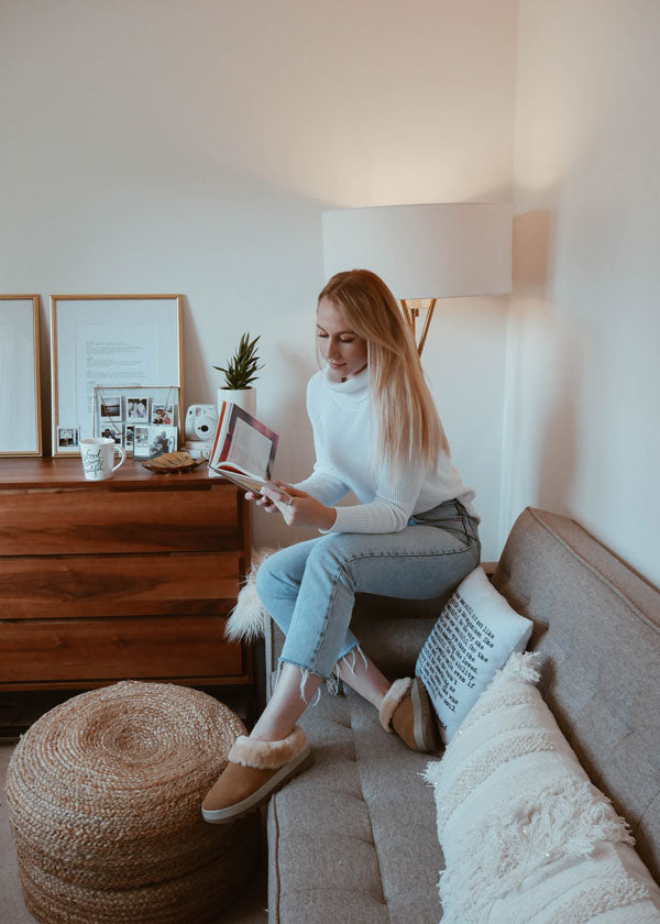 Amanda Weldon reading book on the arm of a couch wearing Cougar Prony Shearling Mule in Tan