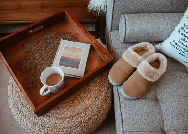 Service tray with coffee, book and Cougar Prony Shearling Mule in Tan on couch