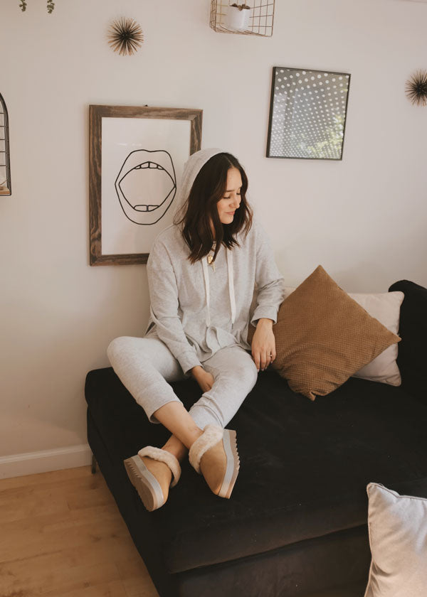 Ana Molina sits on couch wearing Cougar Prony Shearling Mule in Tan