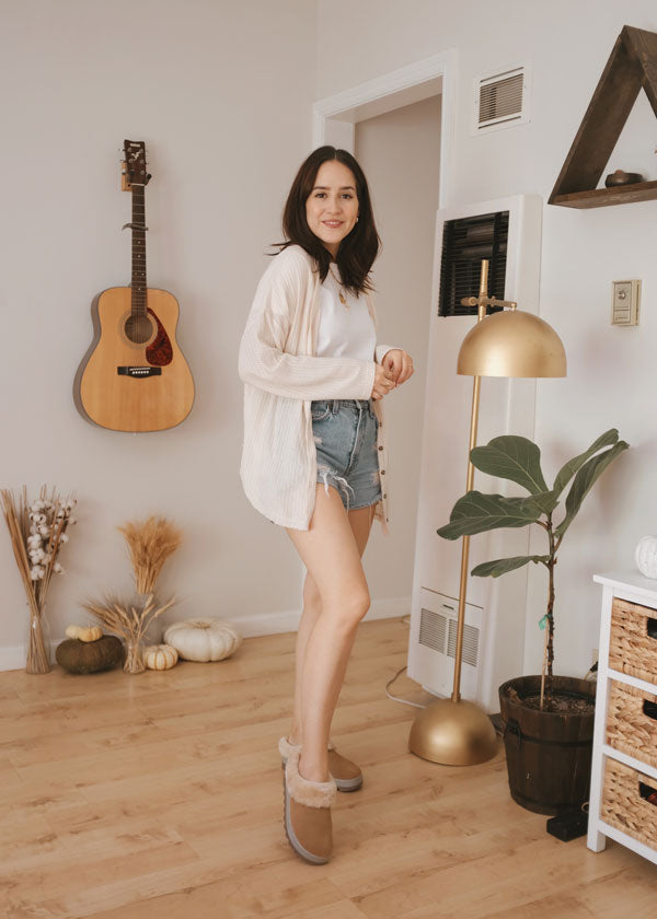 Ana Molina stands in house wearing wearing jean shorts and Cougar Prony Shearling Mule in Tan