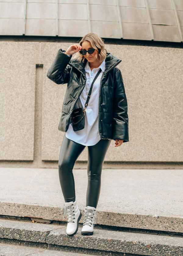 Influencer wearing black jacket and pants walking down steps outdoors wearing Cougar Original Pillow Boots in White