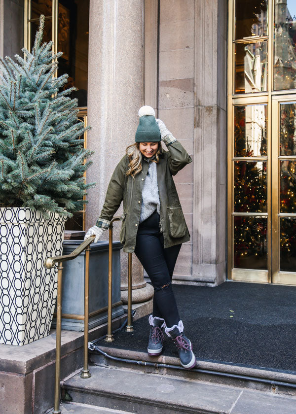 Caroline St Francis outside in New York leaning on railing wearing Cougar Vanetta Suede Mid Boot