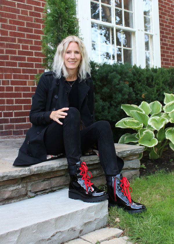Winy Bernard's sitting on steps of house wearing all black with Cougar Gwen Patent Ankle Boot