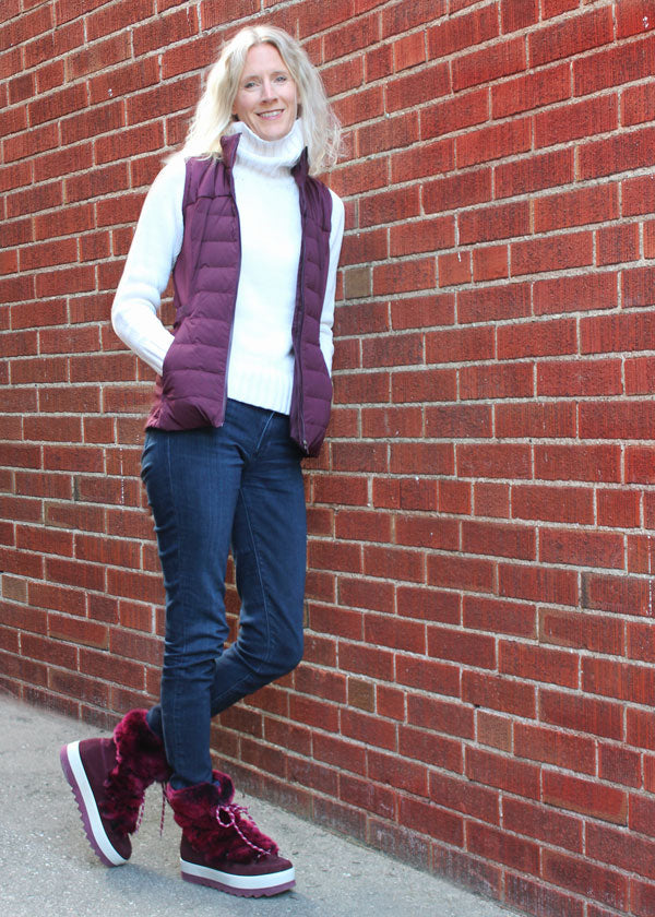 Winy Bernard's leaning against brick wall wearing white shirt, purple vest and blue jeans and Cougar Vanity Suede Winter Boot